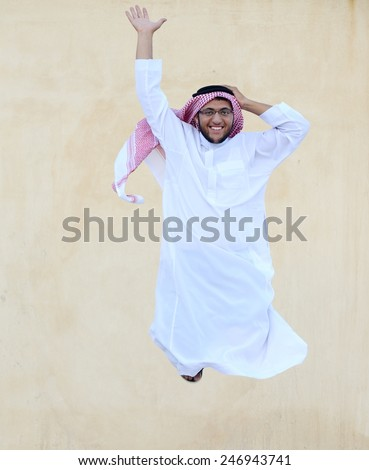 Happy Arabic teenage boy jumping - stock photo