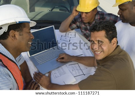 Happy architect and builders discussing with laptop at construction site - stock photo