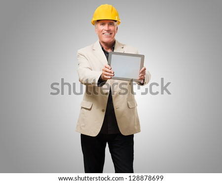 Happy Architect Man Showing Digital Tablet against a grey background - stock photo