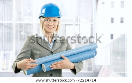 Happy architect woman in protective hat with work plan handheld, smiling at camera.? - stock photo