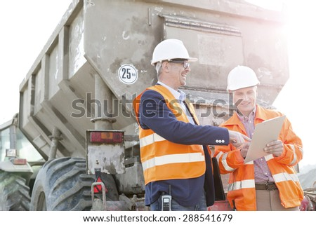 Happy architects discussing over clipboard by construction truck - stock photo