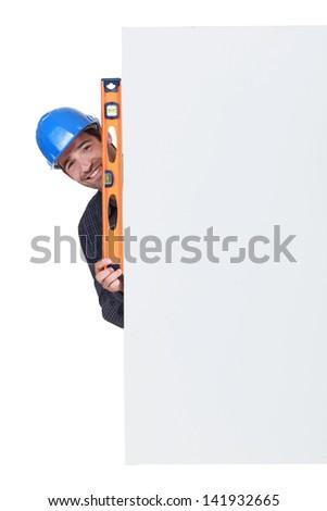 Happy artisan holding spirit-level - stock photo
