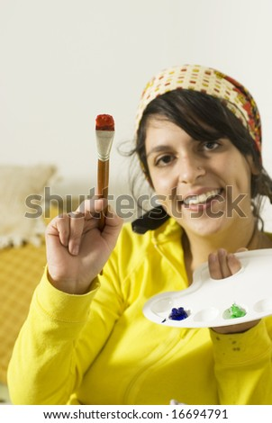 Happy artist smiles as she holds up a paint brush with red paint on it. Vertically framed photo.