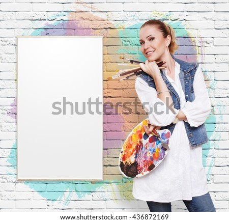 Happy artist. Woman artist with art tools. Female painter with brushes and palette. Empty picture at colorful brick wall with copy space. Fine art. Art classes for adults, education concept. - stock photo