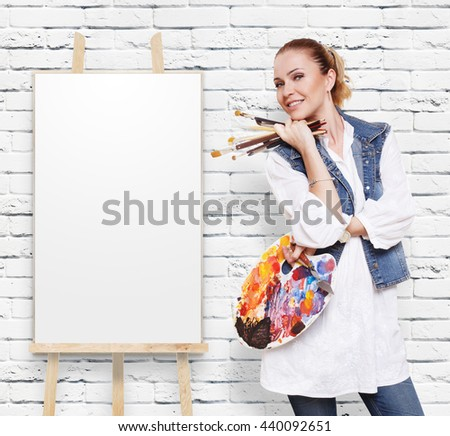 Happy artist. Woman artist with art tools. Girl painter with brushes and palette. Empty canvas at easel at white brick wall with copy space. Fine art. Art classes for adults, education concept. - stock photo