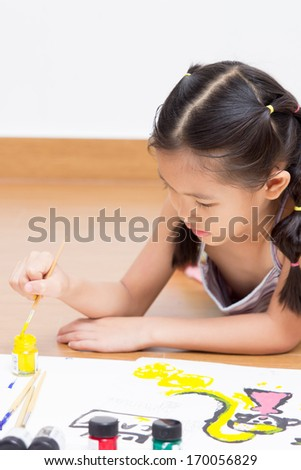 Happy Asian artist child drawing and painting - stock photo