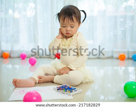 Happy asian baby girl painting with colors in house - stock photo