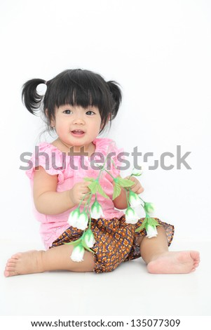 Happy Asian baby girl with Thai traditional dress holding with white flowers on white isolate