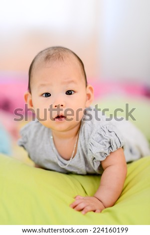 Happy Asian baby on bed.