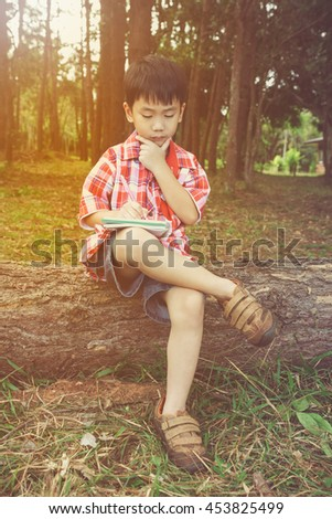 Happy asian boy can resolve problem at park. Outdoors in the day time with bright sunlight. Children planning and education concept. Warm tone and vintage picture style.