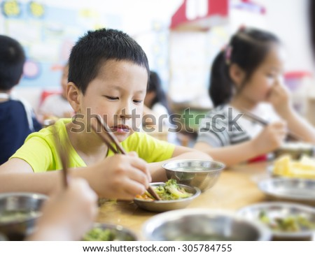 Happy asian boy eating food at pre-school,China