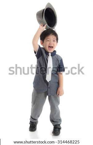 Happy asian boy holding a hat on white background isolated - stock photo