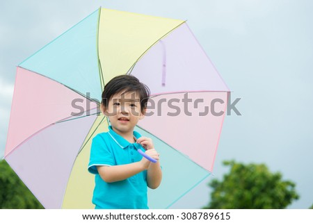 Happy asian boy holding colorful umbrella playing in the park with sky background - stock photo