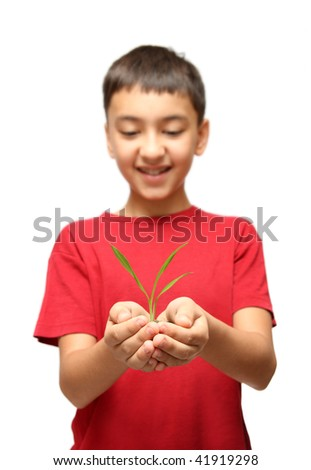 happy asian boy holding green plant in hands - stock photo