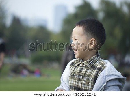 happy asian boy in park with big smile