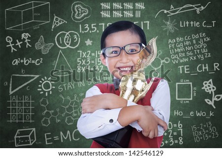 Happy Asian boy is holding trophy in classroom - stock photo