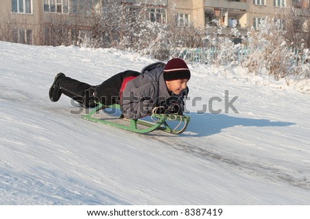 happy asian boy on sledge in bright winter day - stock photo