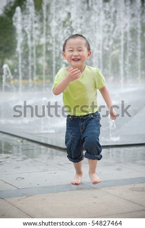 happy asian boy play by Fountain - stock photo