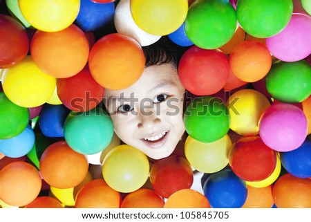 Happy asian boy playing with colorful balls, shot at playground - stock photo