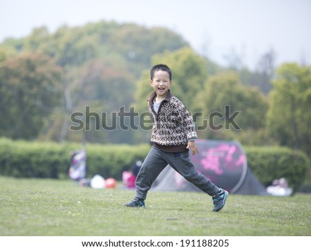 Happy Asian boy running on the grass
