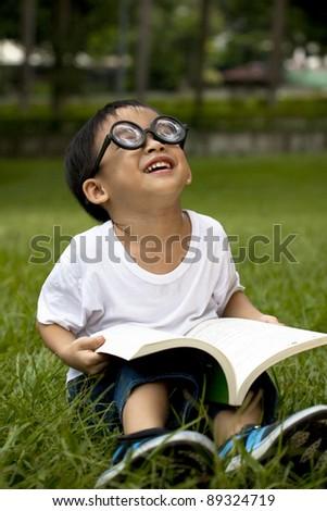 happy asian boy study on the green grass - stock photo