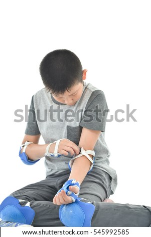 Happy Asian boy wearinghand guard for playing roller blades on white.