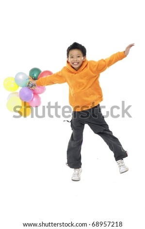 Happy asian boy with colorful balloons jumping - stock photo