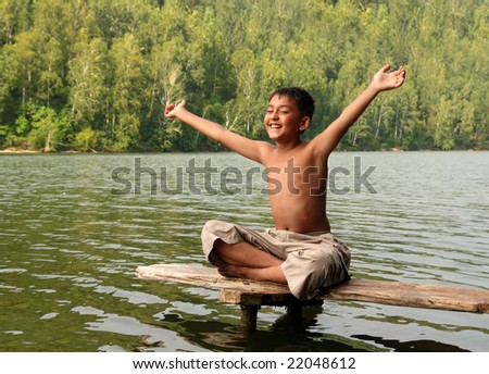 happy asian boy with hands up on stage in lake - stock photo