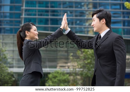 Happy Asian business people doing a high five. - stock photo