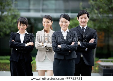 Happy Asian business team standing together with there leader. - stock photo