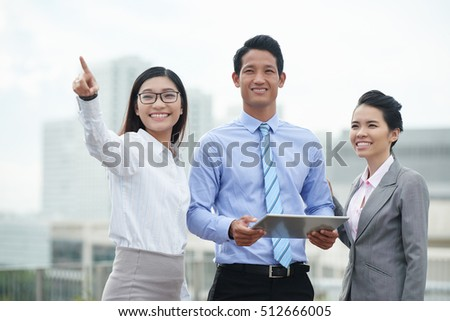 Happy Asian business team with tablet computer standing outdoors