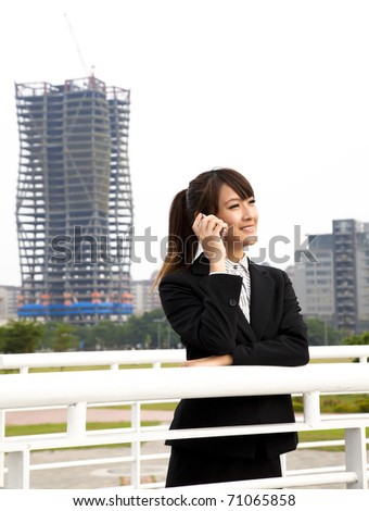 Happy asian business woman talking on the phone and office building background - stock photo