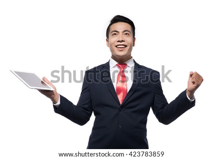 Happy asian businessman celebrating his success on white background. Looking up