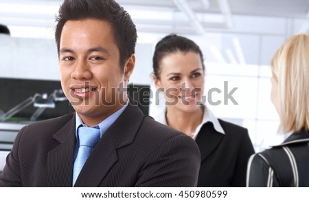 Happy asian businessman in office with colleagues.