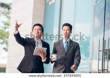 Happy Asian businessman with a digital tablet showing something to his partner - stock photo