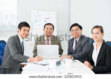 Happy asian businesspeople sitting at table