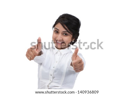 Happy Asian businesswoman gesturing thumbs up against white background - stock photo