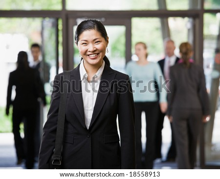 Happy Asian businesswoman holding briefcase in office lobby - stock photo