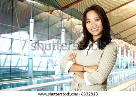 Happy Asian businesswoman in modern corporate building.