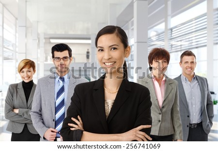 Happy asian businesswoman leading team of business people. - stock photo