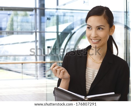 Happy asian businesswoman working in office building. - stock photo
