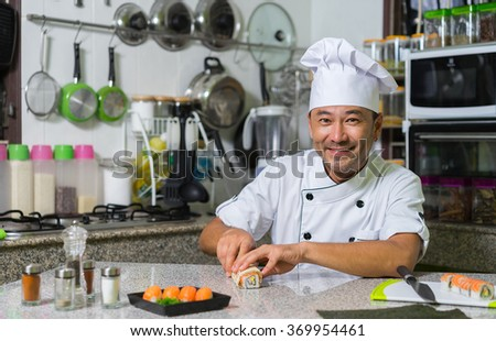 Happy asian chef cooking rolls and sushi on the kitchen. - stock photo