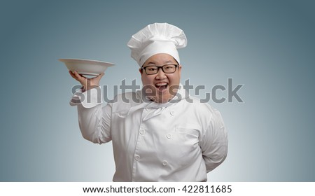 Happy Asian chef with plate in hand - stock photo