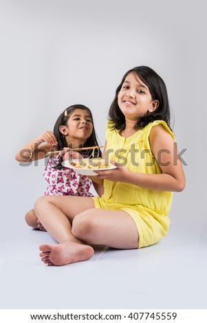 Happy Asian children eating delicious noodle, two cheerful little indian girls eating noodles in white dish isolated over white background - stock photo