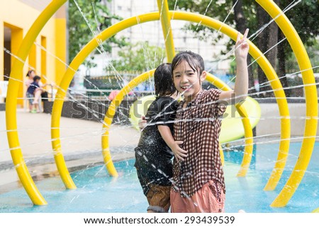 Happy asian children has fun playing in water fountains in water park - stock photo