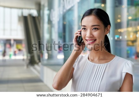 happy asian chinese business woman talking on mobile cell phone at work - stock photo