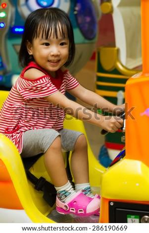 Happy Asian Chinese girl at indoor playground - stock photo