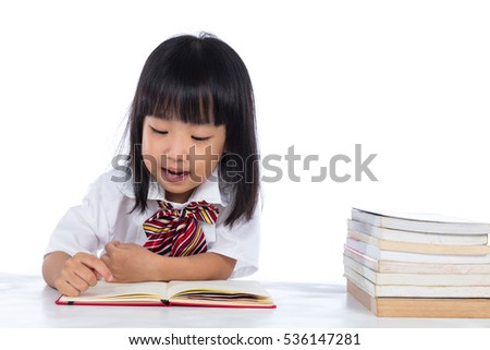 Happy Asian Chinese little girl reading book in isolated white background.