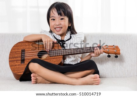 Happy Asian Chinese little girl sitting on the sofa playing ukele