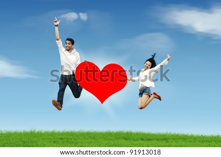 Happy asian couple jumping with a huge heart cutout